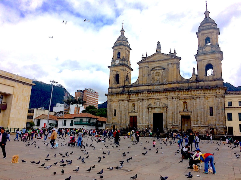 Grand cathedral with a huge plaza filled with people and pigeons in Bogota, Colombia.
