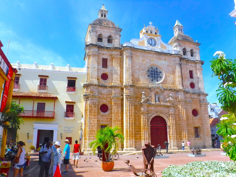 Stone cathedral with a sculpture plaza in front and a bright blue sky, Cartagena, Colombia.