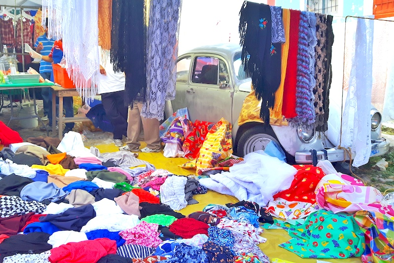 Clothes draped all over an old Volkswagen Beetle at Chapala Market, Mexico.