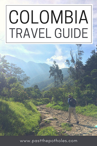 Man walking through sunny valley surrounded by mountains with text: Colombia Travel Guide