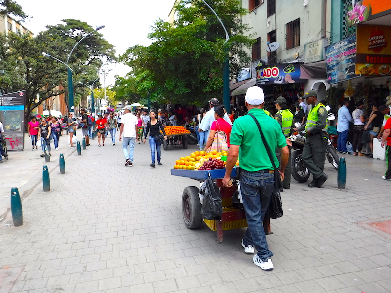 Man walking with a cart full of fruit down a busy pedestrian street in Medellin, Colombia.
