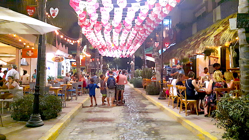 Cobble street lined with restaurants and pink and white banners overhead in Sayulita, Mexico.