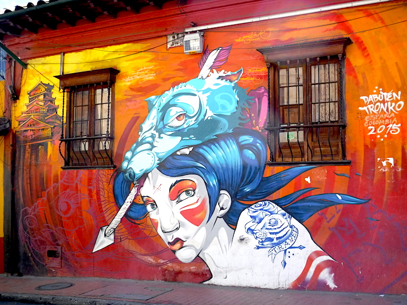 Street art of a girl with alien on her head and a red background in Bogota, Colombia.