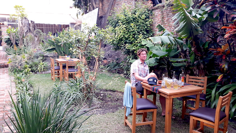 Man sitting at a table in a tropical courtyard in Ajijic restaurant, Mexico.