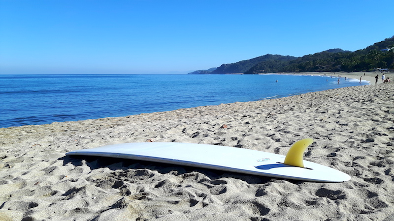 White surfboard laying upside down on the beach in Sayulita, Mexico.
