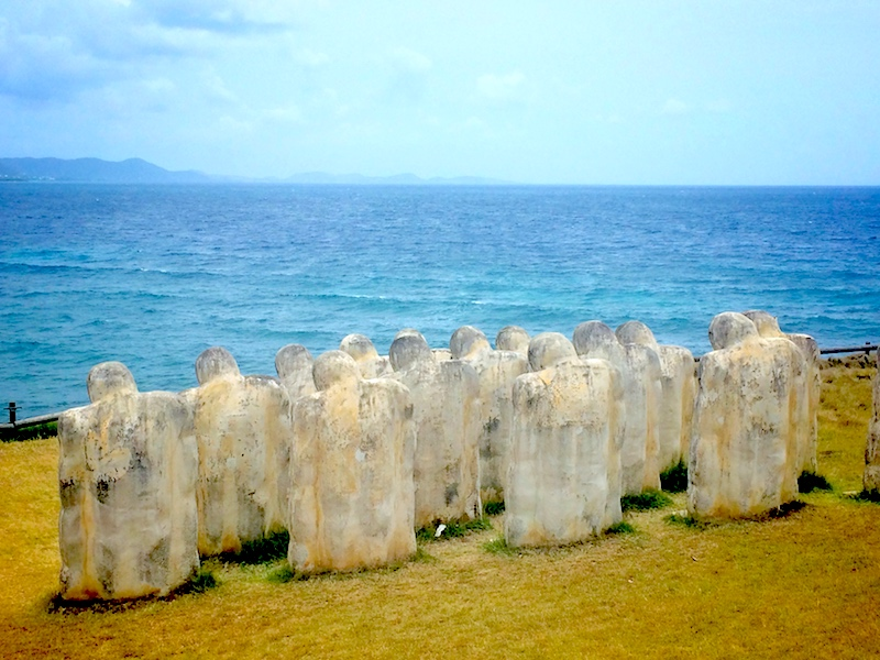 Slave statues at Anse Caffard looking out at the blue Caribbean Sea in Martinique.