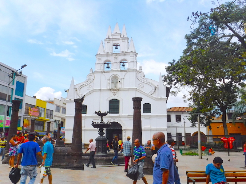 White traditional church in a busy plaza in Medellin, Colombia.