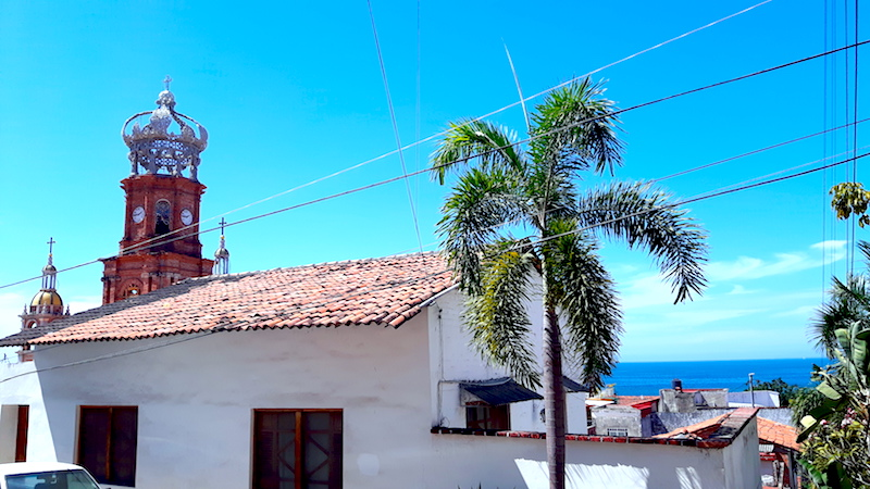 Red tiled roofs and top of cathedral with glimpse of the Pacific Ocean in Puerto Vallarta, Mexico.