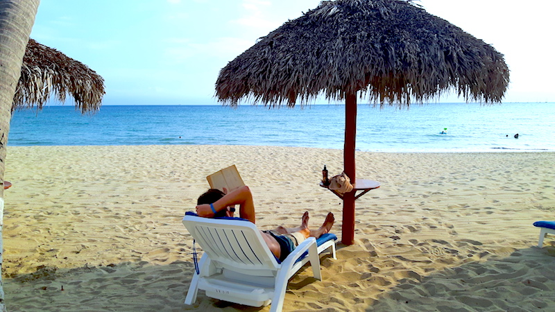 Man on a sun lounger under a palapa reading a book on the beach in Bucerias, Mexico.