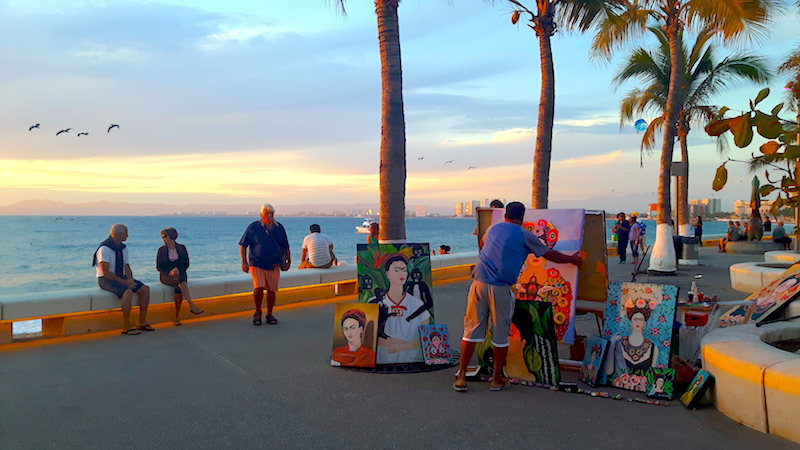 Seller with Frida Kahlo art on the malecon in Puerto Vallarta, Mexico at sunset.