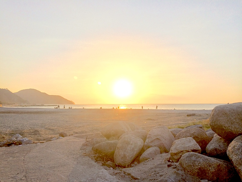 Golden sunset on the beach backed by mountains in Santa Marta, Colombia