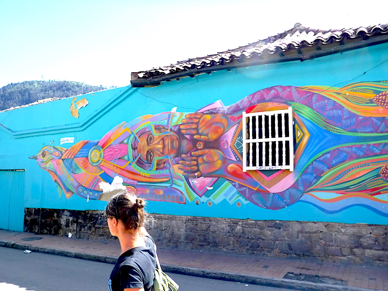 Guide explaining a bright blue indigenous street art on side of colonial building in Bogota, Colombia.