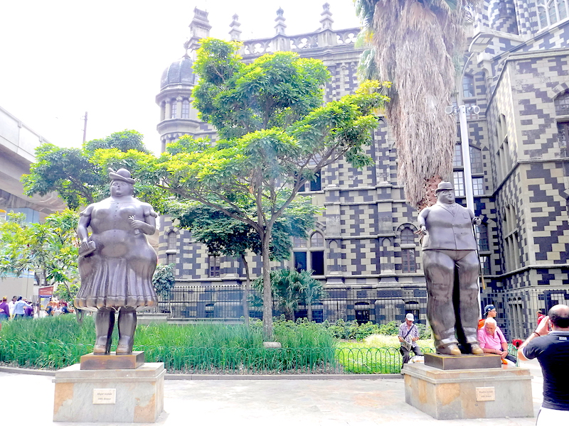 Man and woman Botero sculptures in front of ornate building in Medellin, Colombia.
