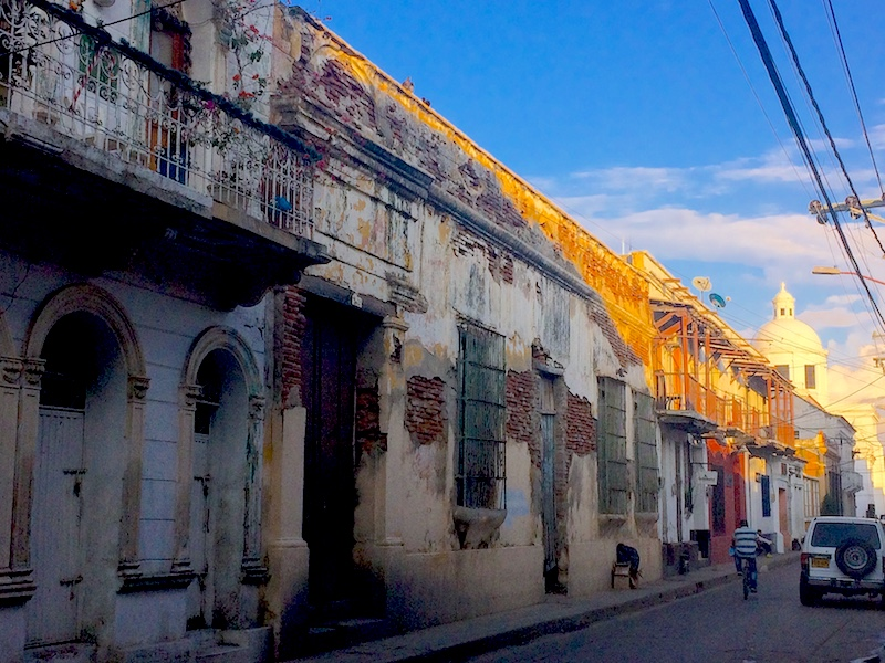 Colonial buildings in the shade with a church spire at the end of the street in Santa Marta, Colombia.