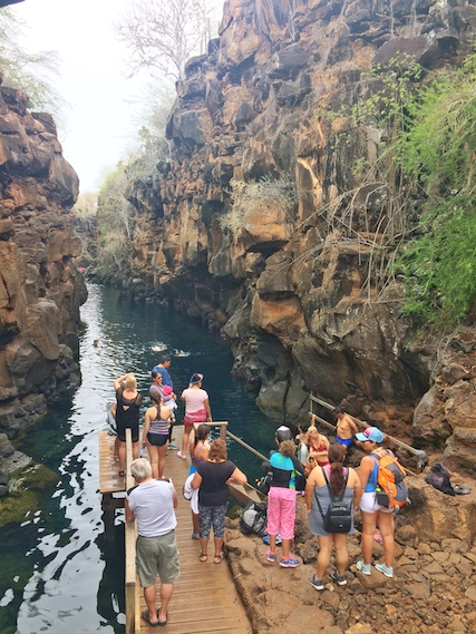 Crowd of people on the dock waiting to get into a narrow channel of water with steep lava rock cliffs on both sides in the Galapagos