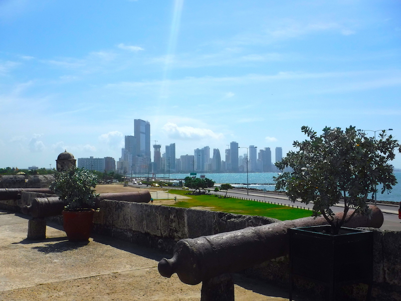 Canons along old city wall of Cartagena, Colombia overlooking modern skyscrapers and Caribbean Sea.
