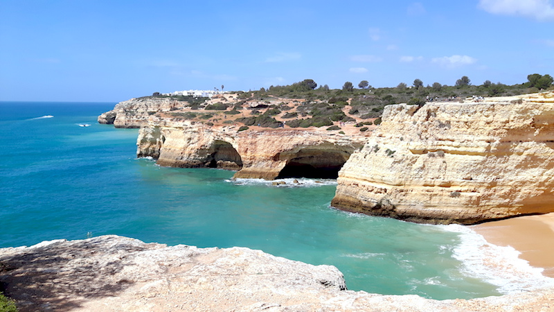 Caves and bays in cliff formations with turquoise water below in Algarve Portugal.