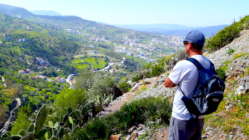 Man standing on a mountainside looking down the valley to Chefchaouen, Morocco.