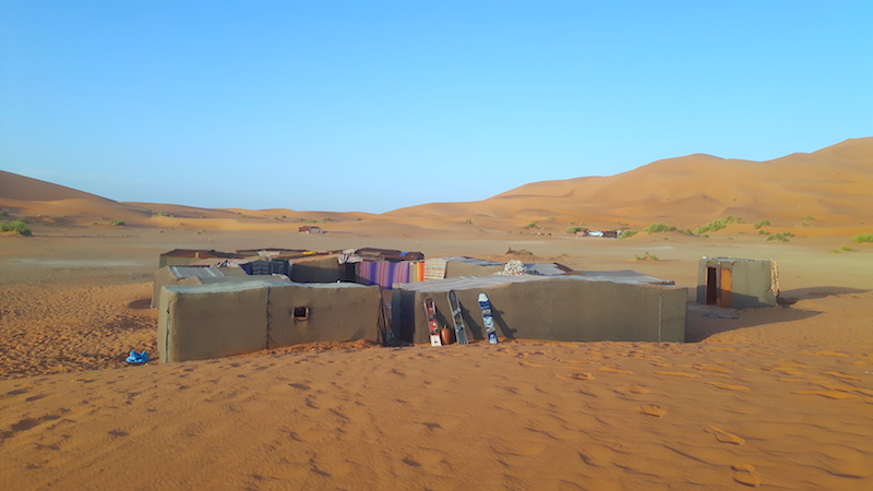 Group of square nomad tents in the middle of orange sand dunes in the Sahara desert, Morocco