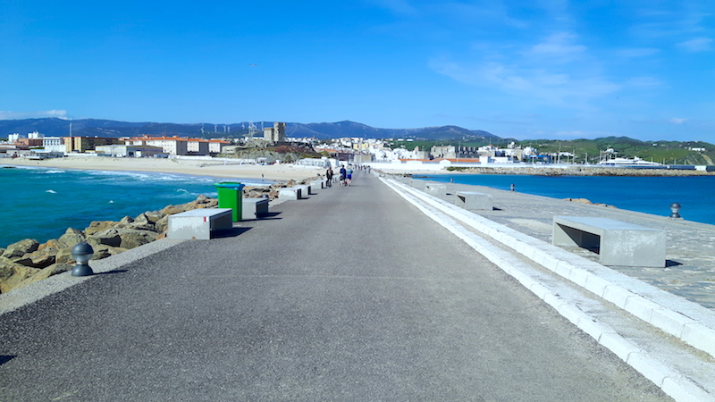 Walkway to an island with Mediterranean Sea on right and choppy Atlantic Ocean on left in Tarifa, Spain.
