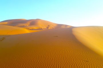 Erg Chebbi sand dunes turn shades of orange at sunset in Sahara Desert Morocco.