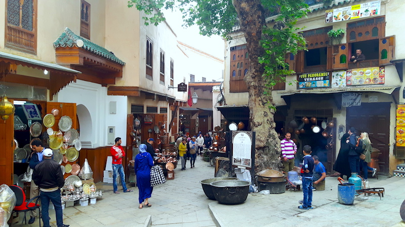 Alley of Fes Medina filled with metal workers and people walking, Morocco.