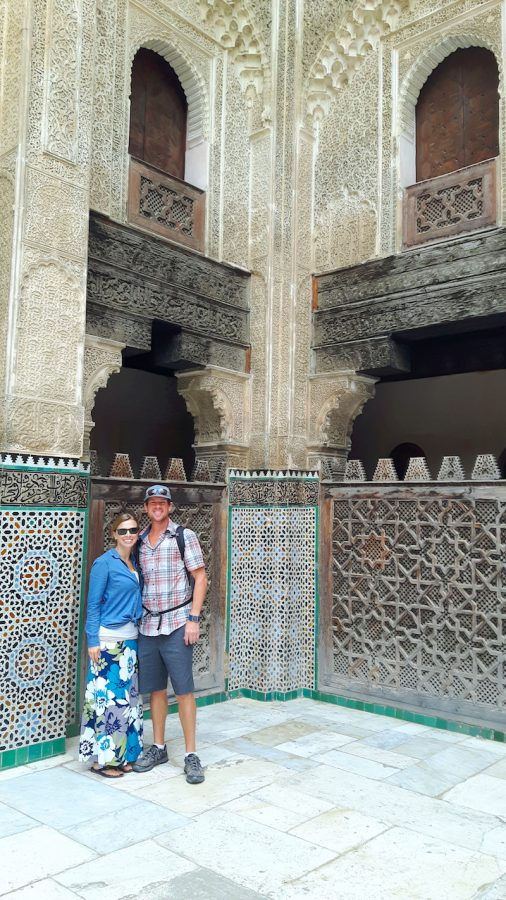 Couple standing inside an intricately carved and tiles mosque in Fes, Morocco.
