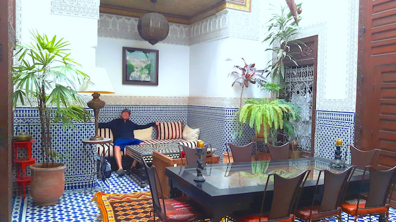 Man relaxing in a beautifully decorated living area in a riad in Fes, Morocco.