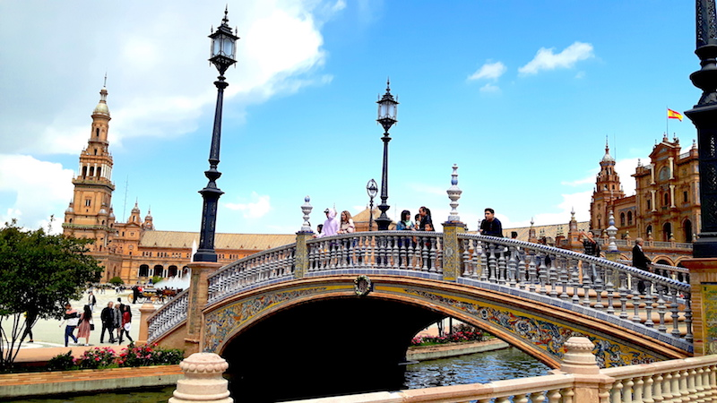 Busy bridge over a large pond in Plaza Espana in Seville Spain.