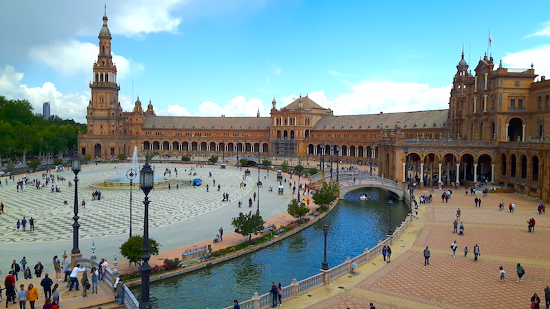 Long, curved building around a central plaza with water features in Seville, Spain.