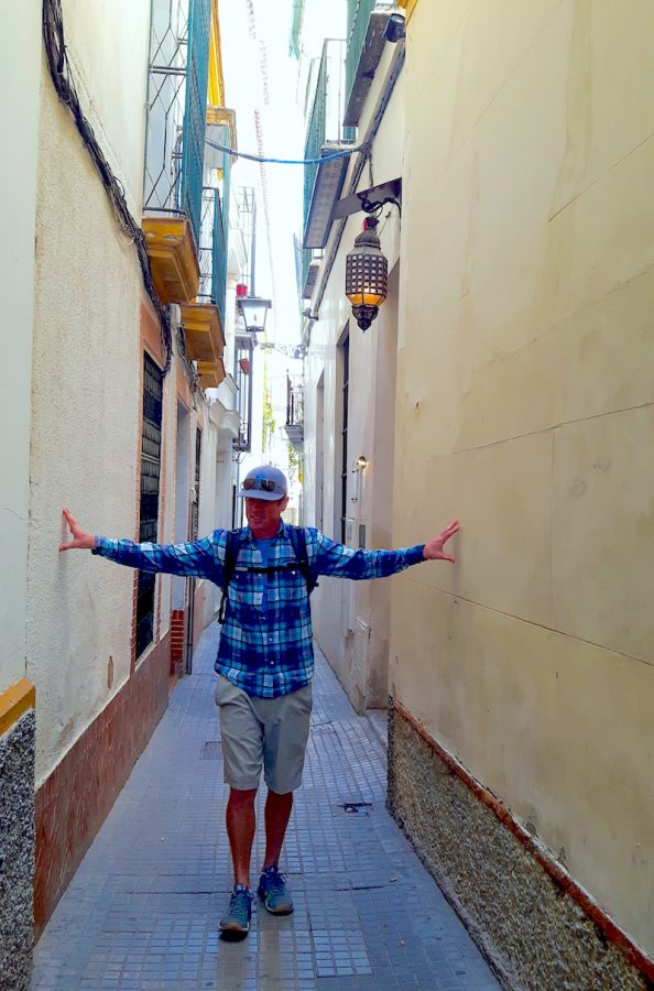 Man touching buildings on each side of a very narrow road in Seville Spain.