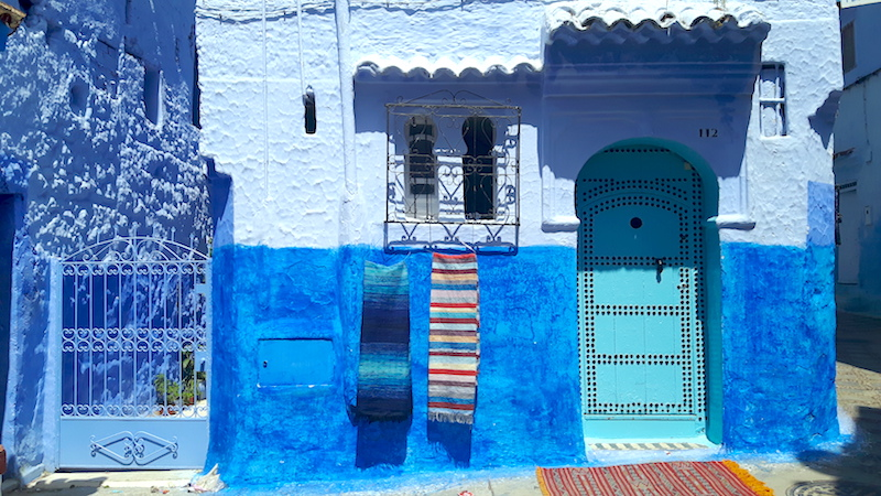 turquoise door with colourful blankets hanging under a window in Chefchaouen, Morocco's Blue City.