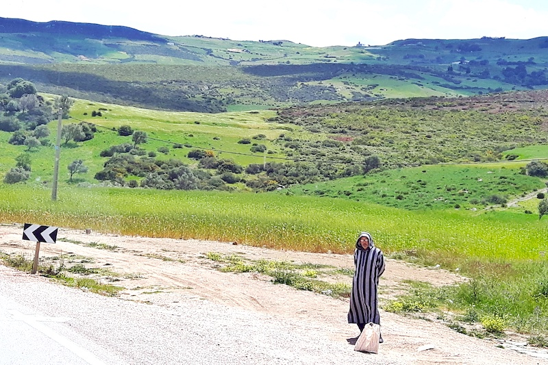 Man in traditional dress waiting on the side of the highway with mountain views behind in Morocco.