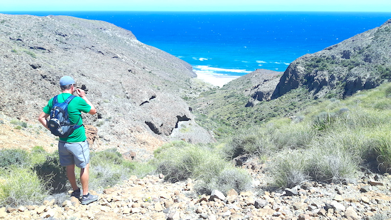 Man looking across a rocky ravine to the bright blue Mediterranean while hiking in Cabo de Gata, Spain.