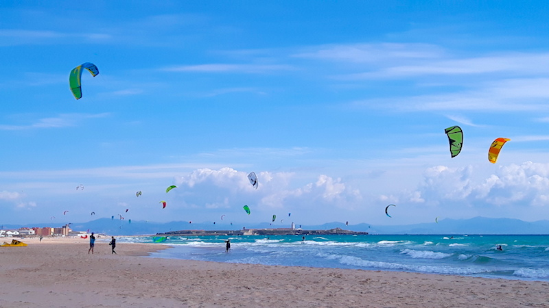 Playa los Lances filled with kites from kiteboarder in the water in Tarifa, Spain.