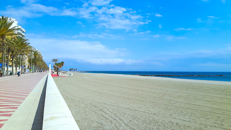 Long empty golden beach with a colourfully tiled promenade running alongside in Almeria Spain.