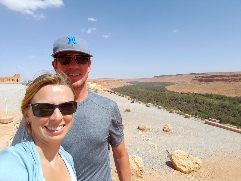 Couple standing in front of green oasis running through a desert valley in Morocco.