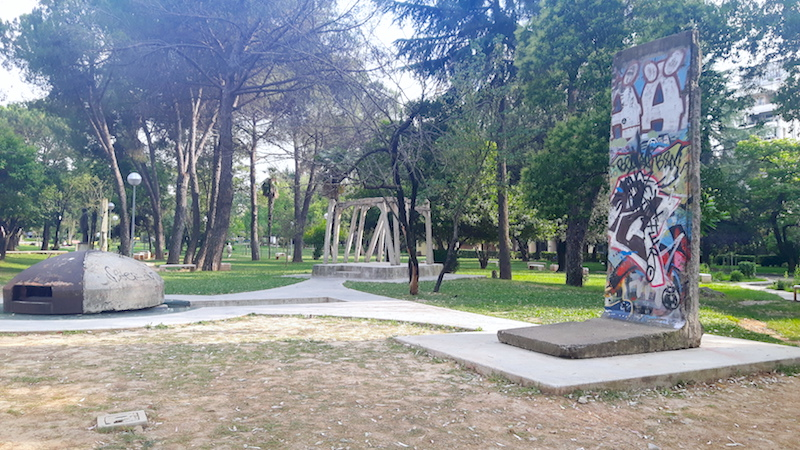 Tirana park with piece of Berlin Wall, old bunker and piece of Checkpoint Charlie on display.