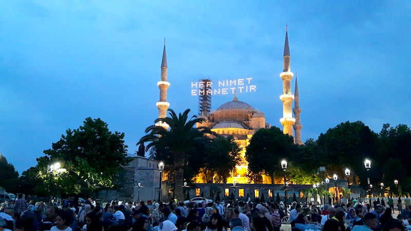 Blue Mosque lit up at sunset with crowds for Ramadan in Istanbul, Turkey.