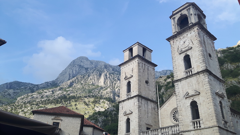 Twin towers of church with tall mountains behind in Kotor, Montenegro.
