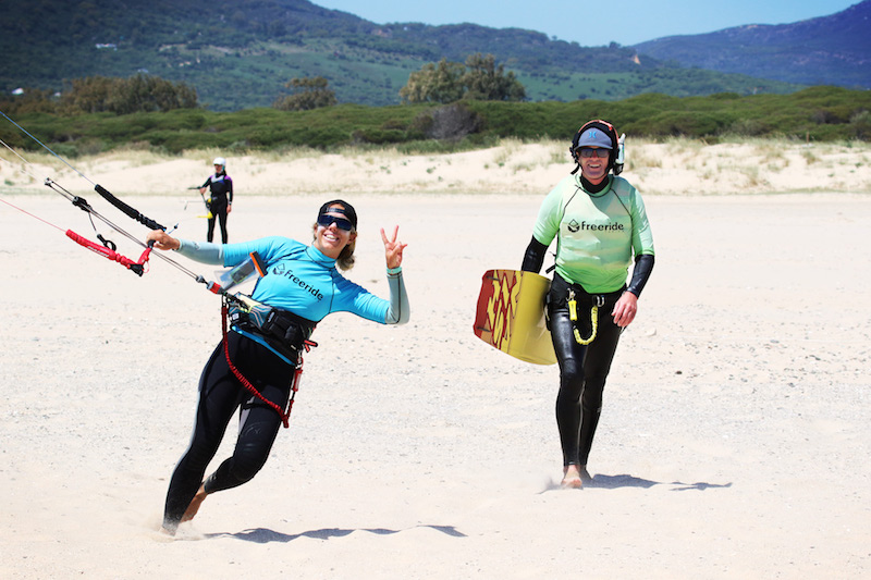 Kitesurfing instructor with blue Freeride Tarifa rash guard and a student with a green one carrying a kite board along the beach in Spain.