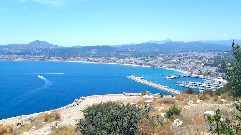 Looking down at Javea harbour with blue water in a long bay in Spain.