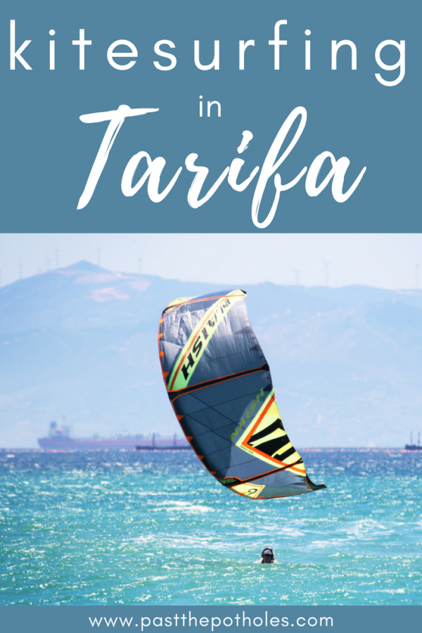 Colourful kite just above the water with the text: kitesurfing in Tarifa.