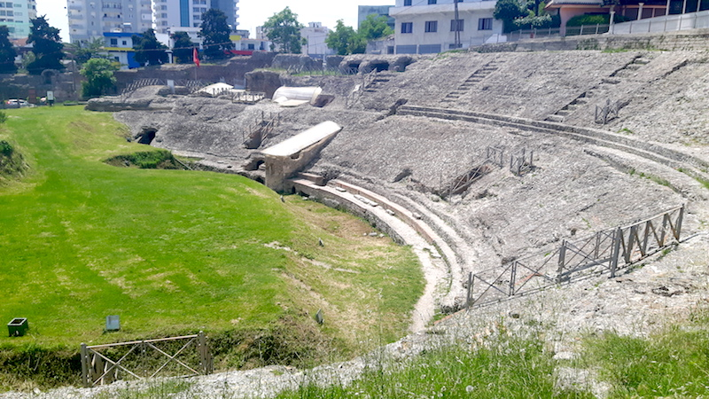 Ancient ruins of a Roman amphitheatre surrounded by modern buildings in Durres, Albania.