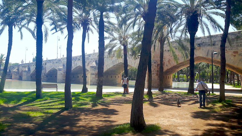 Old stone bridge crossing a dry riverbed turned into a city park in Valencia, Spain.