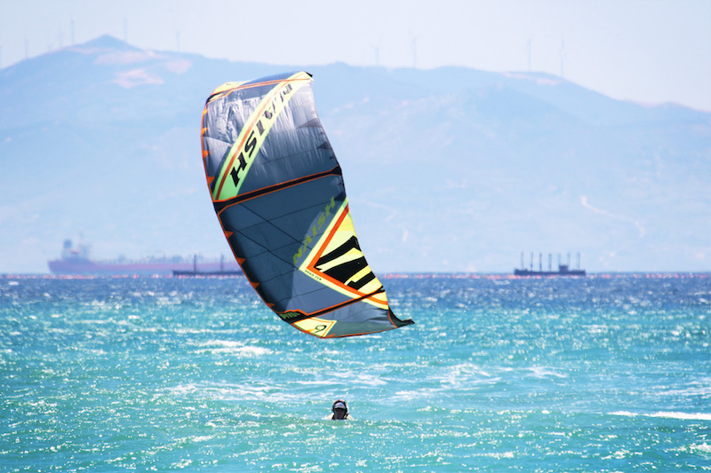 Colourful kite just above the blue water with a head visible in Tarifa, Spain.