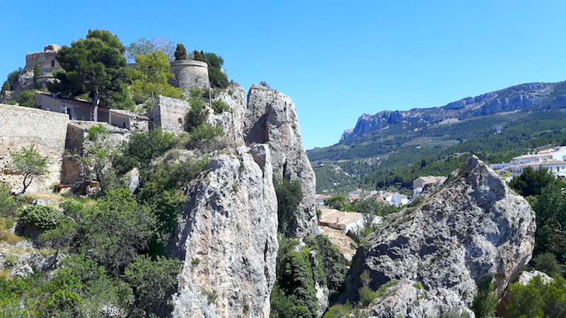 Castle perched on a rocky summit overlooking surrounding landscape in Castell de Guadalest, Spain
