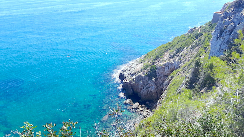 Looking down to clear blue water from cliffs of Montgo, hiking in Denia Spain.
