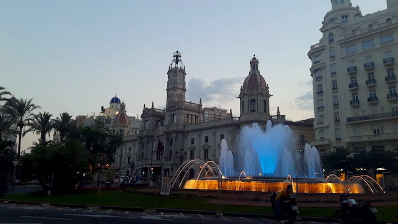 Fountain brightly lit at dusk with grand buildings behind in Valencia, Spain.