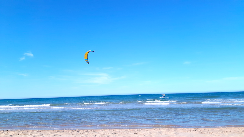 Two people kitesurfing at the beach in Oliva, Spain